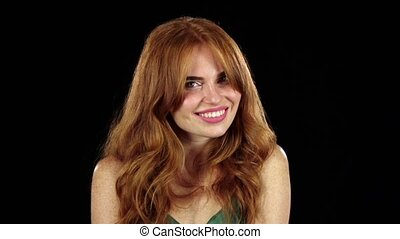 Girl in a freckle smiles a beautiful smile. Black background. Slow motion