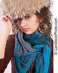 Girl in a fur hat and blue scarf isolated on white background