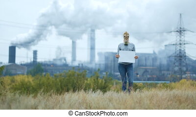 Girl in a gas mask on a background of smoky pipes of a factory