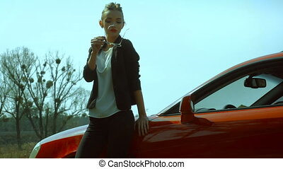 girl in a glasses posing with a red sport car
