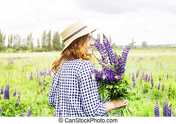 Girl in a green field with flowers blue delphinium