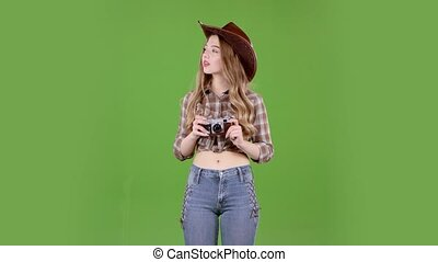 Girl in a hat and cowboy boots and a vest comes with a camera in her hands. Green screen