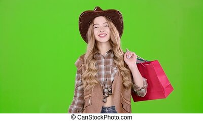Girl in a hat and cowboy boots comes with bags in her hands....
