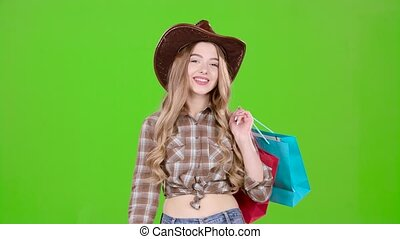Girl in a hat and cowboy boots comes with bags in her hands. Green screen