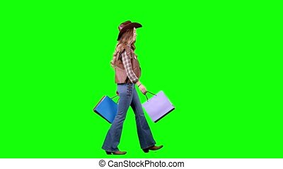 Girl in a hat and cowboy boots comes with bags in her hands. Green screen. Side view