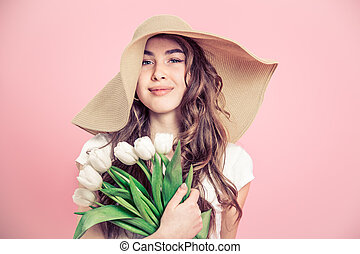 girl in a hat and tulips on a colored background