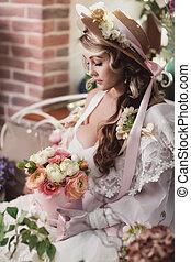 Girl in a hat in a flower arrangement