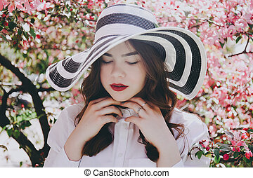 Girl in a hat in blossoming trees.