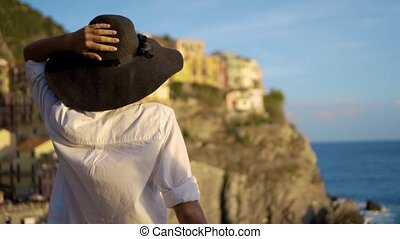 girl in a hat looks at the city of Manarola Italy