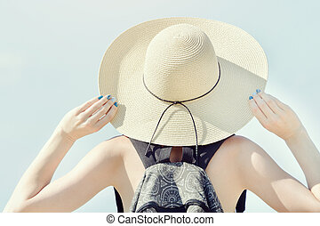 Girl in a hat on a background of clear sky. Back view