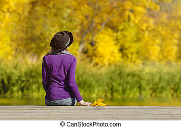 Girl in a hat sits on the dock and admires the colors of autumn. Back view