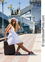 Girl in a hat with a suitcase going on rest