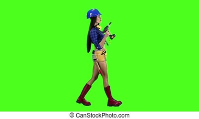 Girl in a helmet and with headphones on her neck goes sideways on a green background. Slow motion