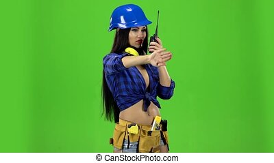 Girl in a helmet with a walkie-talkie on a green background