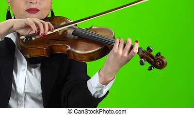 Girl in a jacket playing the violin. Green screen. Close up