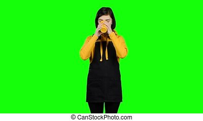 Girl in a jumpsuit drinks tea from a yellow glass. Green...