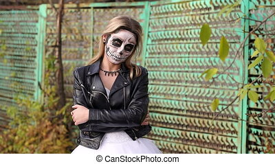 Girl in a leather jacket with makeup for Halloween on background of an old fence