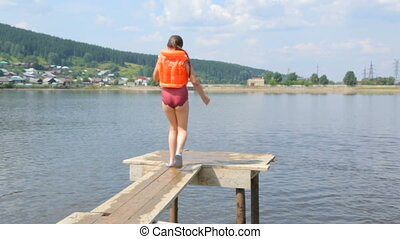 Girl in a life jacket jumping into water