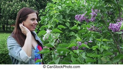 The lilac garden pregnant woman sniffs and admires the flowers of lilac. Spring flowering trees in the Moscow park. Lilac and hawthorn in bloom in the garden in early spring Lilac Garden is the most complete collection of lilac cultivars (varieties) among all Moscow gardens and parks