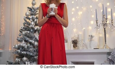 Girl in a long red dress with big lips and seductive eyes blowing a candle