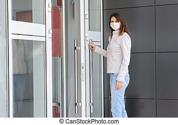 girl in a medical mask near the entrance to the room holds the door handle