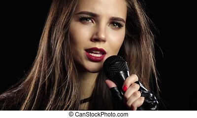 Girl in a microphone sings driving songs and smiles. Black...
