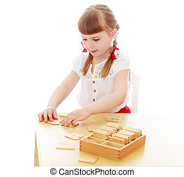 Girl in a Montessori environment - Keen little girl sits at...