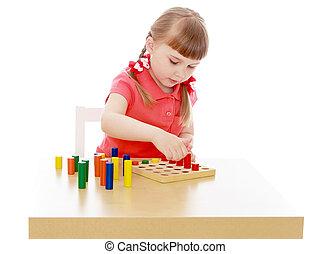 Girl in a Montessori environment - Keen little girl sitting...