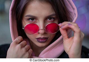 girl in a pink hood adjusts glasses