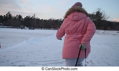 girl in a pink jacket carries sled on the ice, winter...