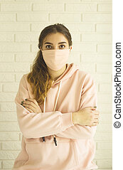 Girl in a pink mask for protection against 2019-ncov covid-19 at home in social isolation.