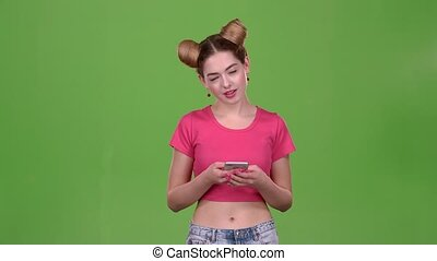 Girl in a pink topic prints a message on the phone. Green screen