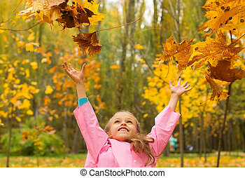 Girl in a raincoat throw yellow leaves up in autumn in the park.
