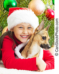 girl in a red Christmas dress hugging dog on the background of t