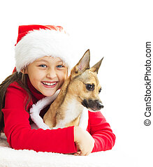 girl in a red Christmas dress hugging dog on white background is