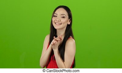 Girl in a red dress flirts, sends kisses and smiles. Green screen
