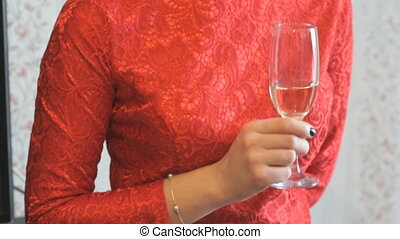 Girl in a red dress holding a glass of champagne