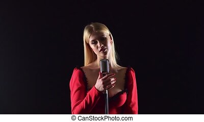 Girl in a red dress is singing into a retro microphone. Black background