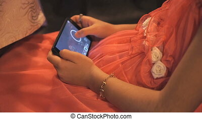 Girl in a red dress playing a game on a phone