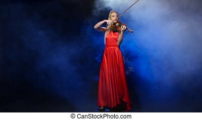 Girl in a red dress playing the violin. Studio. Smoke