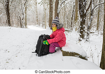 Girl in a red jacket sits on a stone in a winter forest