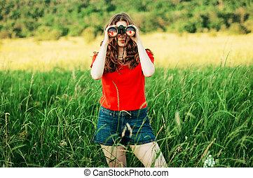 Girl in a red  looking through binoculars. woman looking through