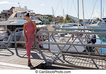 girl in a red striped dress stands at the yacht