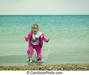 Girl in a red suit throws up sea water.