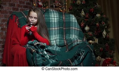 Girl in a red sweater on a chair drinking tea