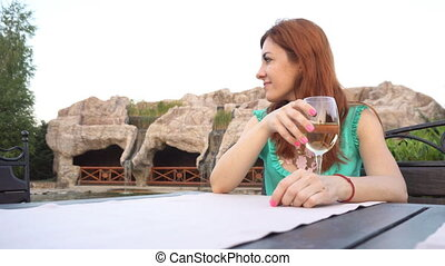 girl in a restaurant on the street drink wine