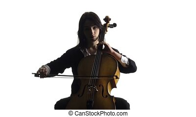 Girl in a room sits and plays a violoncello . White...