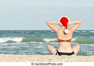Girl in a santa hat sitting on the seashore