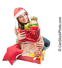Girl in a santa hat sitting with Christmas gifts