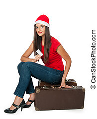 girl in a Santa's helper hat sits on a suitcase
